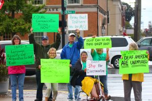 Ben Kleppinger/ben.kleppinger@amnews.com A group of people participating in a protest hold their signs up at the corner of Main and Fourth streets in Danville Thursday morning.