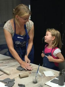 Instructor Catherine Thomsen talks strategy with then-five-year old Lily Kamm during a 2015 Kids Pottery class at the Community Arts Center.