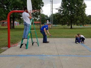 Photo submitted Volunteers and students work at Junction City Elementary, restriping the basketball court and hanging new backboards outside the school.