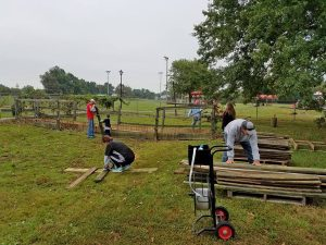 Photo submitted Volunteers remove a bridge that was used to cross a dip in the outdoor area beside Junction City Elementary School.