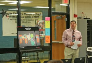 Kendra Peek/kendra.peek@amnews.com Assistant Superintendent Chris Holderman opens the Boyle County Middle School forum, standing in front of a potential depiction of the interior of the new middle school in the cafeteria of the current school.