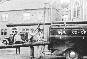 Linemen with REA load  a utility poles on a truck to place for electricity in rural Boyle  County.