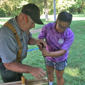 Photo submitted Dora Swann tries her hands hands at  carpentry 1800's style during an educational day at the Abraham Lincoln Birthplace National Monument in Hodgenville, with the help of a park volunteer.