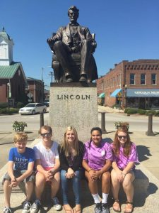 Photo submitted  Landry Woodrum, Tyler Mattingly, Delaney Simpson, Dora Swann, and Lyndsey Bell, on tour to Hodgenville, posing with the Abraham Lincoln Statue by Augustus St. Gaudens on the square in Hodgenville, home of the Abraham Lincoln Birthplace National Monument