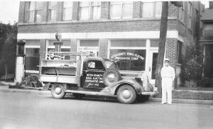 Harry J. Achee, superintendent of the Inter-County Electric Cooperative Corporation, stands by a utility truck.