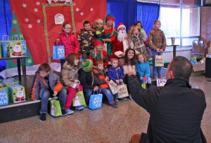 Boyle County High School Principal Will Begley gathers Kentucky School for the Deaf students to take a group photo with the visiting elves, Santa and a reindeer on Friday.