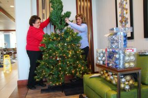 Ben Kleppinger/ben.kleppinger@amnews.com Myrna Miller, left, and Melissa Fightmaster set up a Christmas tree in the lobby of Danville's new Holiday Inn Express Thursday afternoon. Miller is director of sales for the hotel and Fightmaster is the general manager.