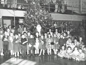 Santa's Visit to Rogers Hall in 1958 – The younger children gathered in front of the big tree in the gymnasium (Rogers Hall) to welcome Santa to the KSD campus.  The pupils began leaving for a two-week Christmas vacation just after Santa's visit.
