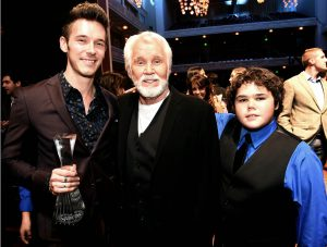 "(Photo by Rick Diamond) Kenny Rogers, center, just accepted the coveted CMT Artist of a Lifetime Award during the 2015 show, with Sam Palladio (left, from ""Nashville"") and Rogers' son, Jordon, at right."