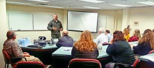 Lincoln County Sheriff's Sgt. Ryan Kirkpatrick discusses with PBK Bank staff possible ways to respond to an active shooter situation Monday morning.