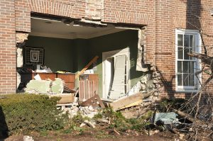A Nissan SUV crashed through the front of the Horky House, taking out a section of the wall. (Photo by Robin Hart)