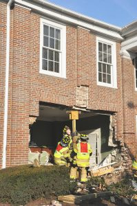 Danville firefighters reinforce the outer wall of the Horky House with wooden girders to ensure no collapse. (Photo by Robin Hart)