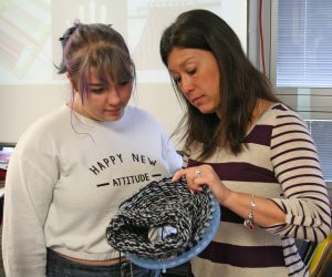 Kendra Peek/kendra.peek@amnews.com Delaney Sallee and art teacher Shelly Stinnett work on a loom project at the Danville High School, making a hat to donate.