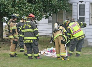 Kendra Peek/kendra.peek@amnews.com Firefighters spray a fire extinguisher on smoldering clothes outside a home Lausman Avenue in Junction City. Firefighters from Junction City were called to the house at about 10:52 a.m. Wednesday when residents had to evacuate due to smoke.