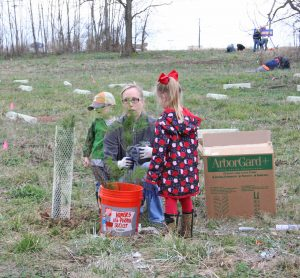 Kendra Peek/kendra.peek@amnews.com Jessica Glasscock and her kids, Nolan, left, and Joslyn, right, were part of the group planting trees on Saturday.