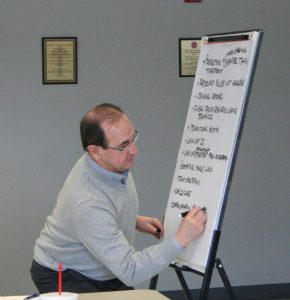 Kendra Peek/kendra.peek@amnews.comKendra Peek/kendra.peek@amnews.com Steve Rhinehart, chairman of the Danville-Boyle County Workforce Development Committee, writes part of the list on paper during the community-wide meeting.